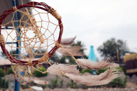 Dream catchers develop in the wind against the backdrop of the beach. A lot of space in the frame creates a feeling of calm and serenity, and developing dream catchers create a sense of security.