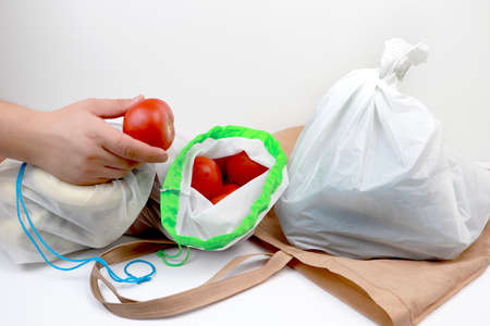 Plastic bag and eco natural reusable tote bag for shopping with vegetables and fruits. The concept of a conscious choice in favor of reusable things and the rejection of disposable plastic goods. Environmental protection, philosophy zero west