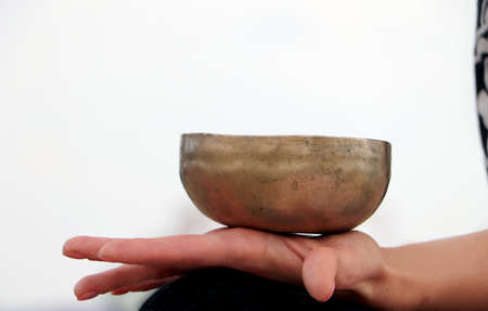 Musical instrument - singing Himalayan bowl. The singing bell holds the girl in his hand. The practice of healing vibrations, surya, yoga, meditation