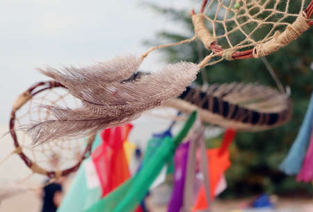 Dream catchers develop in the wind against the backdrop of the beach. A lot of space in the frame creates a feeling of calm and serenity, and developing dream catchers create a sense of security. 版權商用圖片 - 131570594