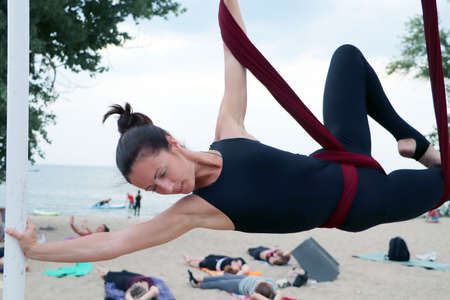 Beautiful girl practices yoga in hammock on the beach. Classes fly yoga in nature, on the seashore. Red canvas and woman in black bodysuit