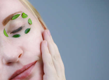 Eyes of a girl with green leaves. Moisturizing, beauty and skin care. The concept of natural and organic cosmetics