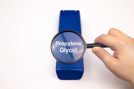 Chemical components on the shampoo label: Propylene Glycol. A hand holds a blue jar and a magnifier, where the harmful ingredients of a detergent are written in close up.