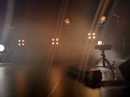 Concert stage and lighting fixtures on it, musical equipment. Smoke from a smoke installation gently breaks yellow light and creates the effect of a gentle glow. Zdjęcie Seryjne