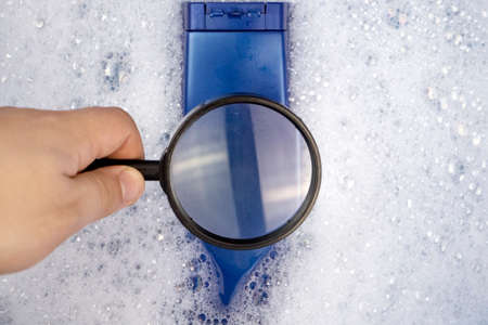 Chemical components on the shampoo label. A hand holds a blue jar and a magnifier, where the harmful ingredients of a detergent are written in close up. Place for an inscription.