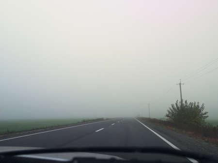 Foggy road and road markings. Horizontal image. Bad visibility