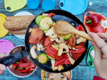 Picnic and nature: flat lay photography. On a blue vintage table is a burner with a frying pan, plates with food. The cook fries and cooks vegetables, mushrooms and meat.