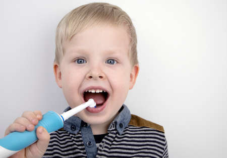 Four year old child brushes his teeth with an electric brush. The boy on a white background laughs and holds a toothbrush. The concept of baby teeth and oral hygiene