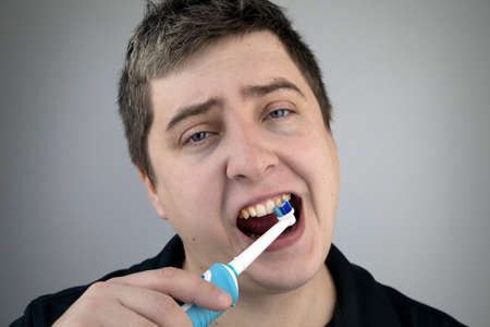 Sleepy man brushes his teeth with an electric brush. Oral hygiene concept. Tired man caring for teeth