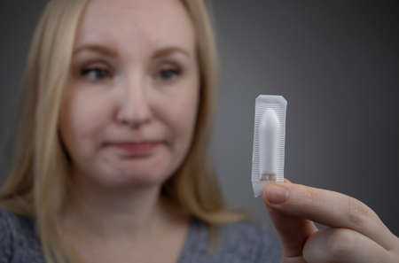 Vaginal or rectal suppository in the hands of a woman. The drug is in the form of suppositories. The concept of treatment of gynecological diseases and diseases of the rectum Stock Photo