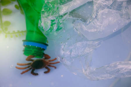 Small crab entangled in a plastic bag. Plastic pollution of the oceans. Ecology and environment protection concept Stock Photo
