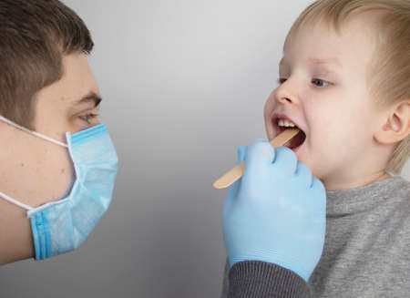 An otolaryngologist examines a child's throat with a wooden spatula. A possible diagnosis is inflammation of the pharynx, tonsils or pharyngitis. The concept of treatment and prevention of childhood diseases