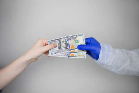 Patient's hand holds out money to the doctor. The concept of corruption in healthcare, bribery or paid medicine