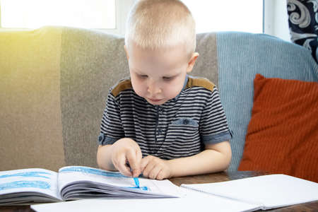 Preschooler is engaged in home schooling. The boy sits at a table, writes, draws and learns online on the Internet. Quarantine due to the coronavirus pandemic, covid-19 Reklamní fotografie