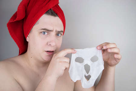 Funny man with a red towel puts a moisturizing fabric mask on his face. The concept of men's personal care, spa treatments and the use of men's cosmetics Reklamní fotografie