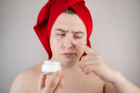 Funny man with a red towel on his head sniffs, tastes and smears a cream on his face. The concept of male self-care, spa treatments and male cosmetics