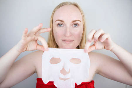 A cheerful and funny girl fooling around and grimacing in a moisturizing face mask. Morning beauty treatments, oily and combination skin care concept.