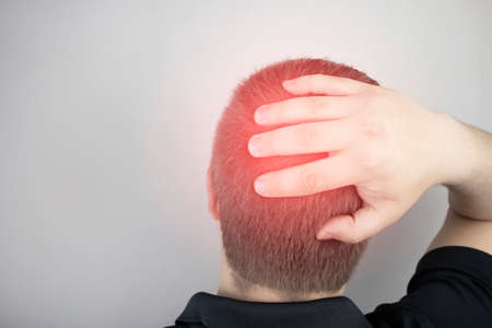 A man suffers from pain in the back of his head. Signs of cervical osteochondrosis, spondylosis, myositis, or hypertension. The concept of acute pain in different parts of the body Stock Photo