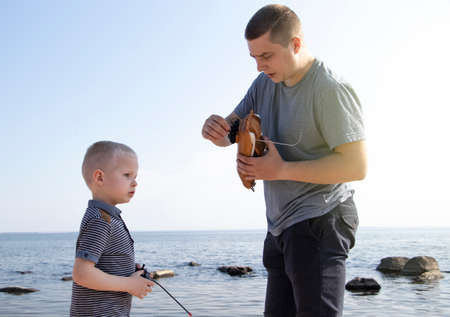 Dad and son launch a ship on the radio. Father shows the boy how to play with the boat on the remote control. The concept of relaxing on the beach and a happy childhood Stock fotó
