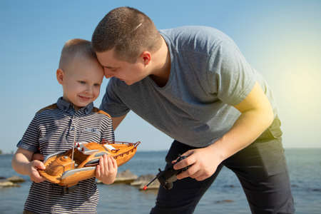 Dad and son launch a ship on the radio. Father shows the boy how to play with the boat on the remote control. The concept of relaxing on the beach and a happy childhood