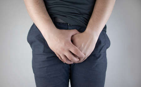 Man front view. Pain in the groin and bladder. The concept of pain in men as a result of prostatitis, inflammation of the bladder or genitourinary system. Frequent urination.