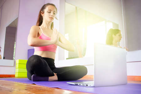 Fitness and yoga trainer teaches via laptop. Wireless technology in sports, self-isolation . The girl shows exercises in the gym on the mat. The concept of distance learning.