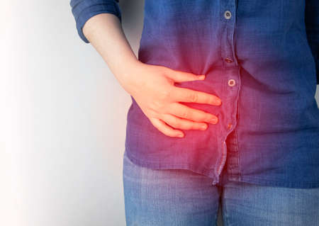 A woman suffers from pain in the appendix. Acute appendicitis, Crohn's disease, or inflammatory bowel disease. Surgeon examination and preparation for laparoscopic appendectomy