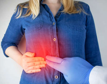 A woman grabs his right side under the ribs. Pain in the liver. Pain syndrome in liver disease. Hepatologist examination