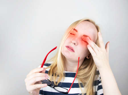 A woman rubs his tired eyes with his hands on a white background. The concept of eye fatigue from the computer and fatigue from work. Pain in the eyes and forehead, migraine, eye diseases