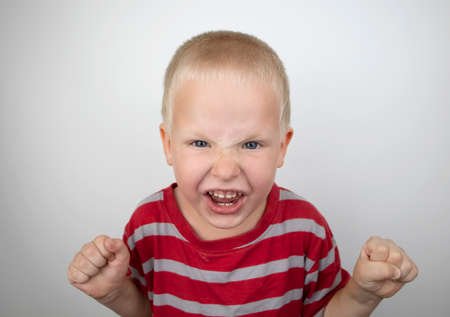 Angry boy screaming and hysteria on a white background. Four-year-old child shows child aggression Banco de Imagens