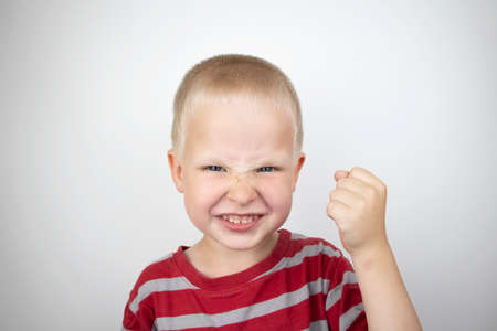 Angry boy screaming and hysteria on a white background. Four-year-old child shows child aggression Foto de archivo