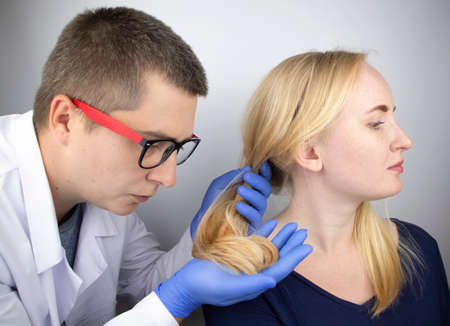 A doctor trichologist conducts a study of the hair of a blonde. Alopecia treatment. Hair loss, alopecia, itching, burning in the head, seborrhea or brittle ends