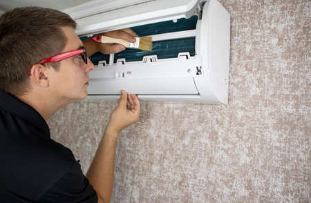 Cleaning the air conditioner from dust, mold and dirt. An air conditioner maintenance worker assesses the level of contamination, cleans the radiator and flushes out contamination from cavities.