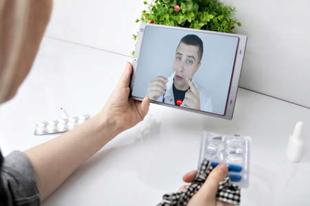 A woman communicates via a tablet with a doctor via video link. Medical assistance under quarantine conditions. Remote consultation with a therapist