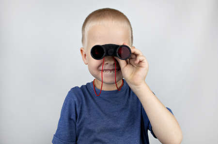 A boy with binoculars looks into the distance and smiles. Facial expression and body position show victory. The concept of vision for success, business confidence and overcoming difficulties.
