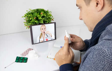 A man communicates via a computer with a doctor via video link. Medical assistance under quarantine conditions. Remote consultation with a therapist