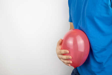 Conceptual photography. The man holds a red ball near his belly, which symbolizes bloating and flatulence. Then he brings a needle to it to burst the balloon and thus get rid of the problem.