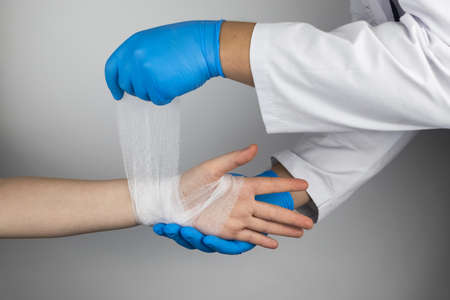 The traumatologist puts a bandage on the forearm of the female patient. The concept of help with fractures and sprains. The technique of applying a cruciform bandage.