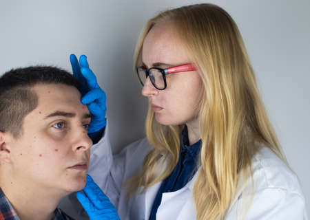 An allergist or dermatologist examines red spots on a man's face.