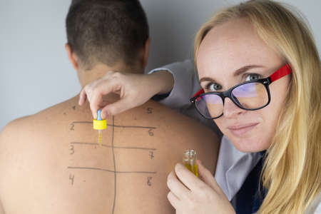 An allergist in the laboratory conducts an allergy prick-test