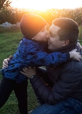 Dad and son hug and indulge in nature. The sun's rays pass through the faces creating a feeling of warmth and affection. Loving parents and happy childhood