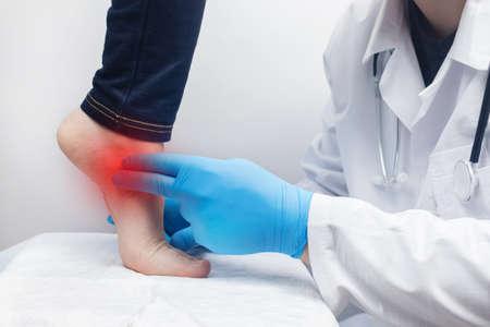 An orthopedic surgeon examines a woman's leg. Foot pain, tendon sprains, inflammation, flat feet, bursitis, fasciitis. Foot disease treatment concept. The doctor examines Standard-Bild