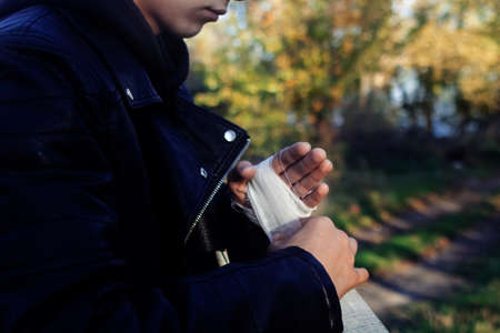 The fighter is bandaging his hands. The concept of preparation for a fight, sports competition, boxing and kickboxing. A man in a leather jacket.