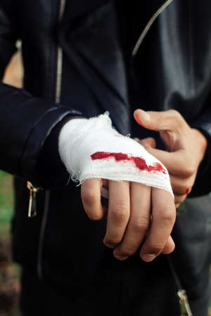 Man with bandage with blood on the knuckles, natural background. End of fight, fight, blood and aggression concept. A man in a leather jacket. Standard-Bild