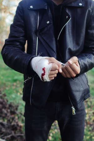 Man with bandage with blood on the knuckles, natural background. End of fight, fight, blood and aggression concept. A man in a leather jacket.