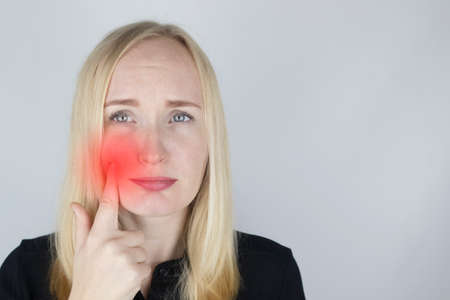 A woman clings to his cheek and winces in pain in his tooth. The concept of dental problems, caries, tooth decay, flux. White background and place for text. On examination by a doctor. Standard-Bild