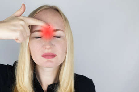 Nasal bridge pain, headache. A woman holds his nose with his hand and winces in pain. Signs of acute ethmoiditis. On examination by a doctor.