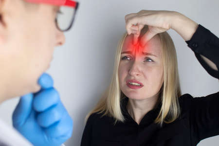 A woman holds his head with his hands. Sensation of headache, migraine and dizziness. Headaches from stress or overwork. On examination by a doctor. Standard-Bild