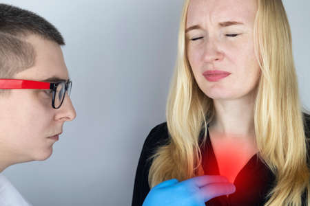 A woman grabs his chest in the region of the heart. Heart attack or chest pain. The concept of heart disease and its pain manifestations. On examination by a doctor.