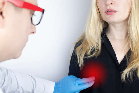 A woman suffers from chest pain. On examination by a gynecologist-mammologist. The concept of the prevention of breast diseases, cancer, mastopathy or hormonal disorders Standard-Bild